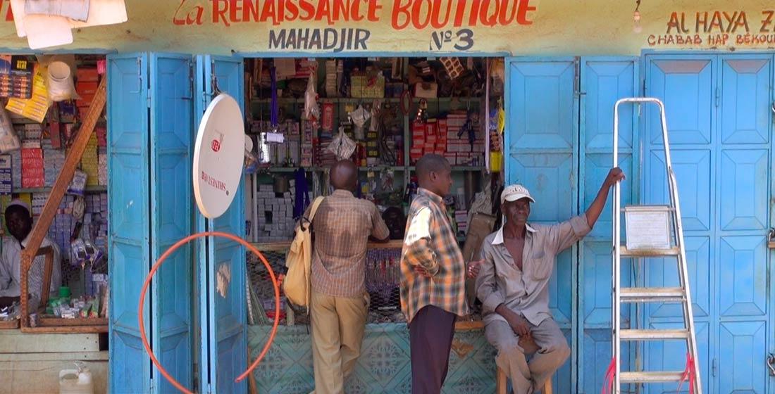 Des hommes devant une boutique dans PK 5, un quartier majoritairement musulman au sein de la capitale. La ville a été longtemps divisée entre chrétiens et musulmans depuis que les Anti-Balaka ont pris les armes contre les Seleka et les musulmans en décembre 2013. 15 septembre 2014 (VOA / Bagassi Koura).